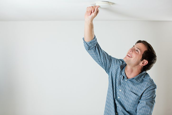 Gill Insurance | Young man testing smoke alarm on ceiling